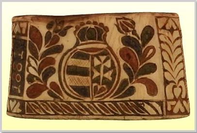 """""""A vörsi pásztor faragta sótartó díszítésének fókusza a virágzó ágakkal/életfákkal ölelt magyar címer. Nem feledkezett meg a tárgy alkotója a stilizált madár és a Nap, valamint a tulipán mellett a kard ábrázolásáról, s a készítés évéről sem."""" (kobzosBBL)"""