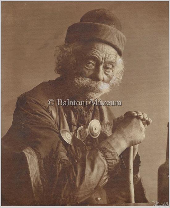 """""""A korabeli fényképen kifinomult esztétikai és szociális érzékenységgel megörökített érett korú kanász időtlen tekintete, hagyományos öltözete, attribútumai a pásztortársadalomban a legkevésbé megbecsült mesterségnek állítanak örök emléket."""" (kobzosBBL)"""